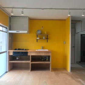 LDKの造作キッチン/イエローペイント。右側は玄関土間です